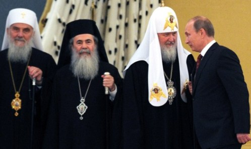 Russian President Vladimir Putin (R) talks with Russia's Patriarch Kiril (2nd R) during a family photo following the meeting with Orthodox leaders at the Kremlin in Moscow on July 25, 2013. AFP PHOTO / POOL / ALEXANDER NEMENOV