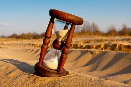 reloj de arena sobre arena fondo