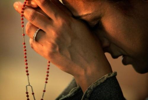 mujer orando rosario