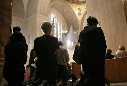 fieles arrodillados en misa