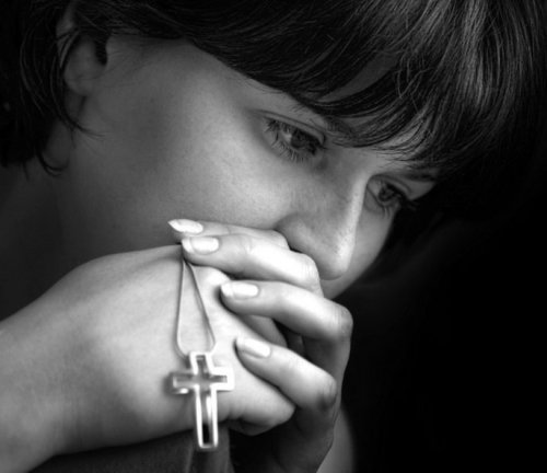 mujer orando con rozario en la mano
