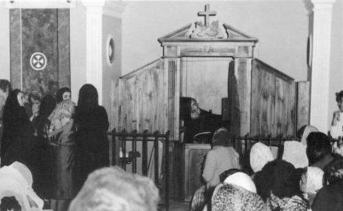 Padre Pio confesando y multitud esperando