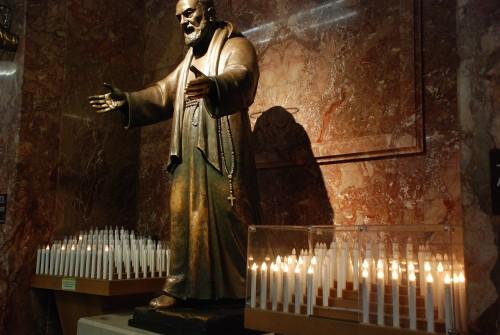 estatua de padre pio con velas fondo