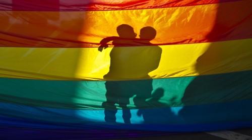 bandera gay y besandose a trasluz fondo