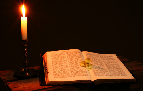 bible book by candle light