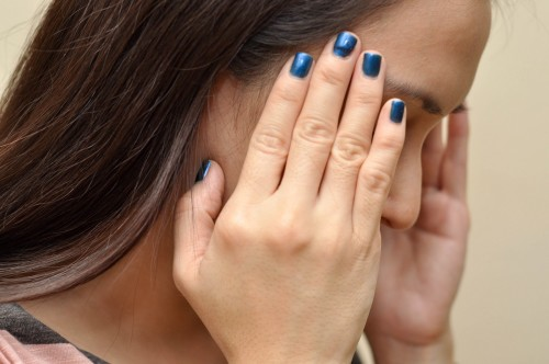 mujer con manos en la sien fondo