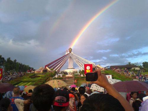 Estatua de Jesus de la Misericordia con arco iris arriba