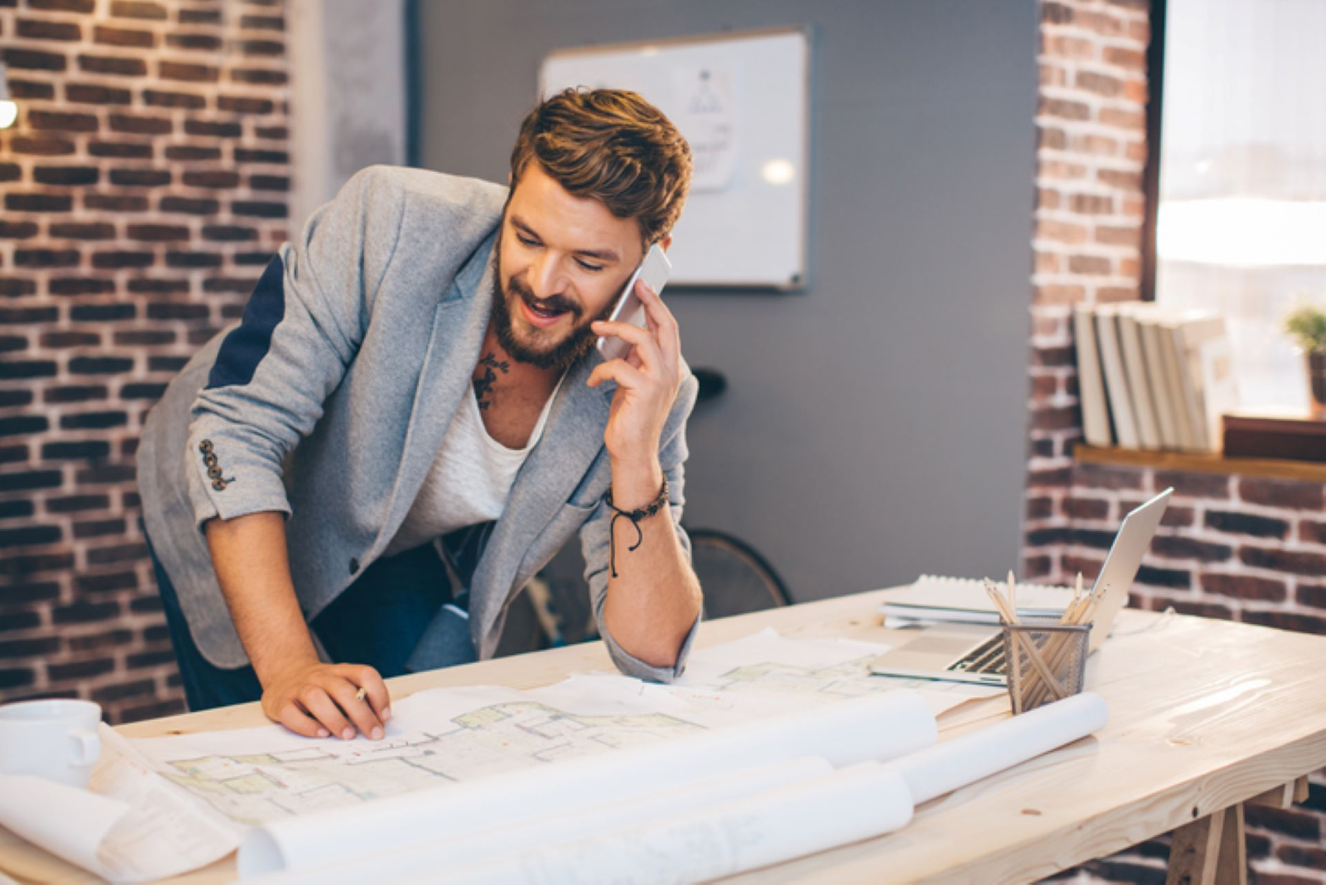man-on-phone-while-leaning-over-table-with-architectural-plans