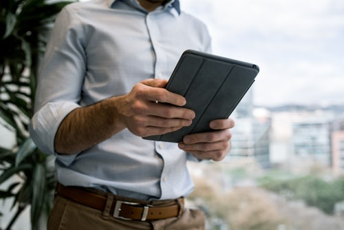 close-up-of-man-on-balcony-holding-tablet