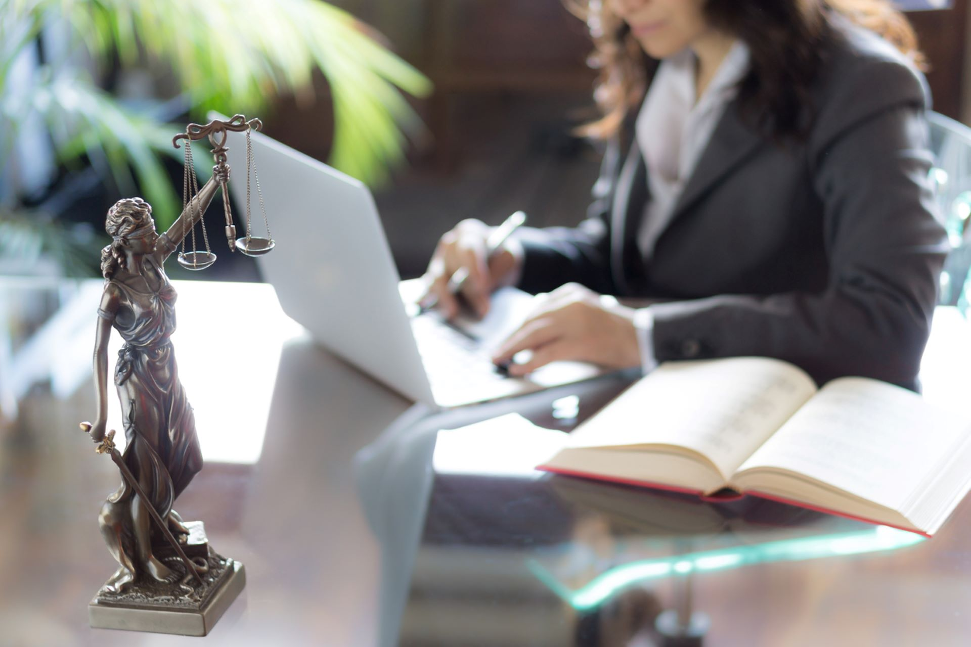 lawyer-typing-on-laptop-at-desk-with-justice-statue-holding-scales