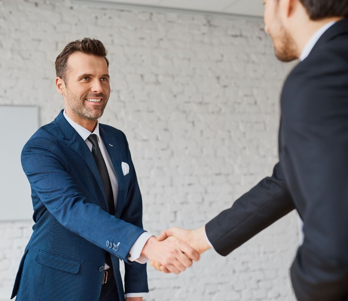 A business man shaking hands with another business man.