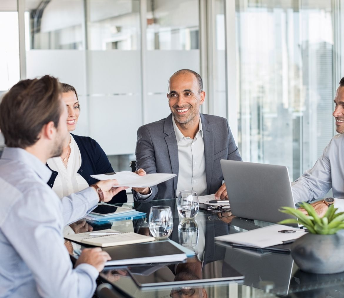 A ceo handing a business man a report in a meeting.