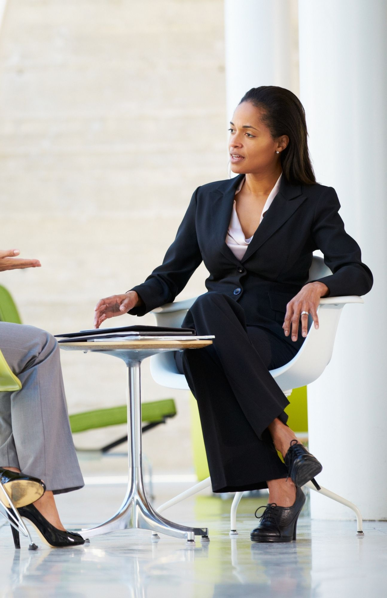 A woman sitting in a 1 on 1 meeting with a coworker.