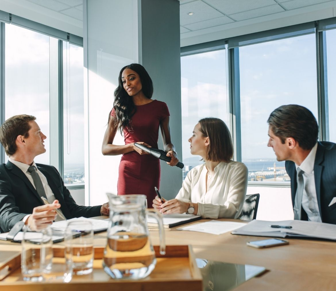 A woman speaking to her boss during a team meeting.