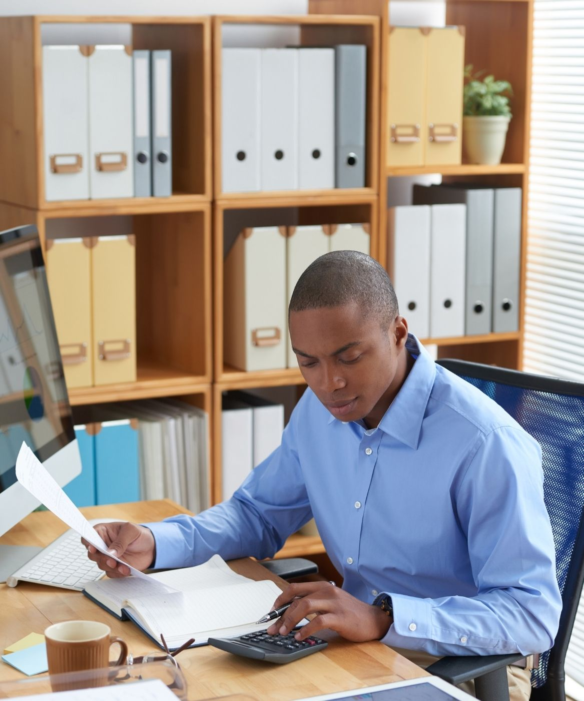 An accountant working on company books in an office
