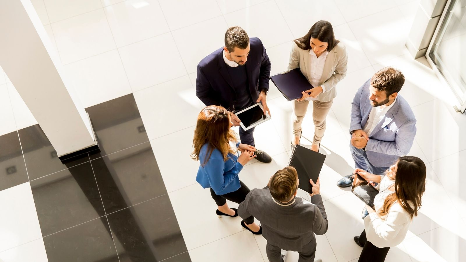 A group of business professionals standing in a meeting
