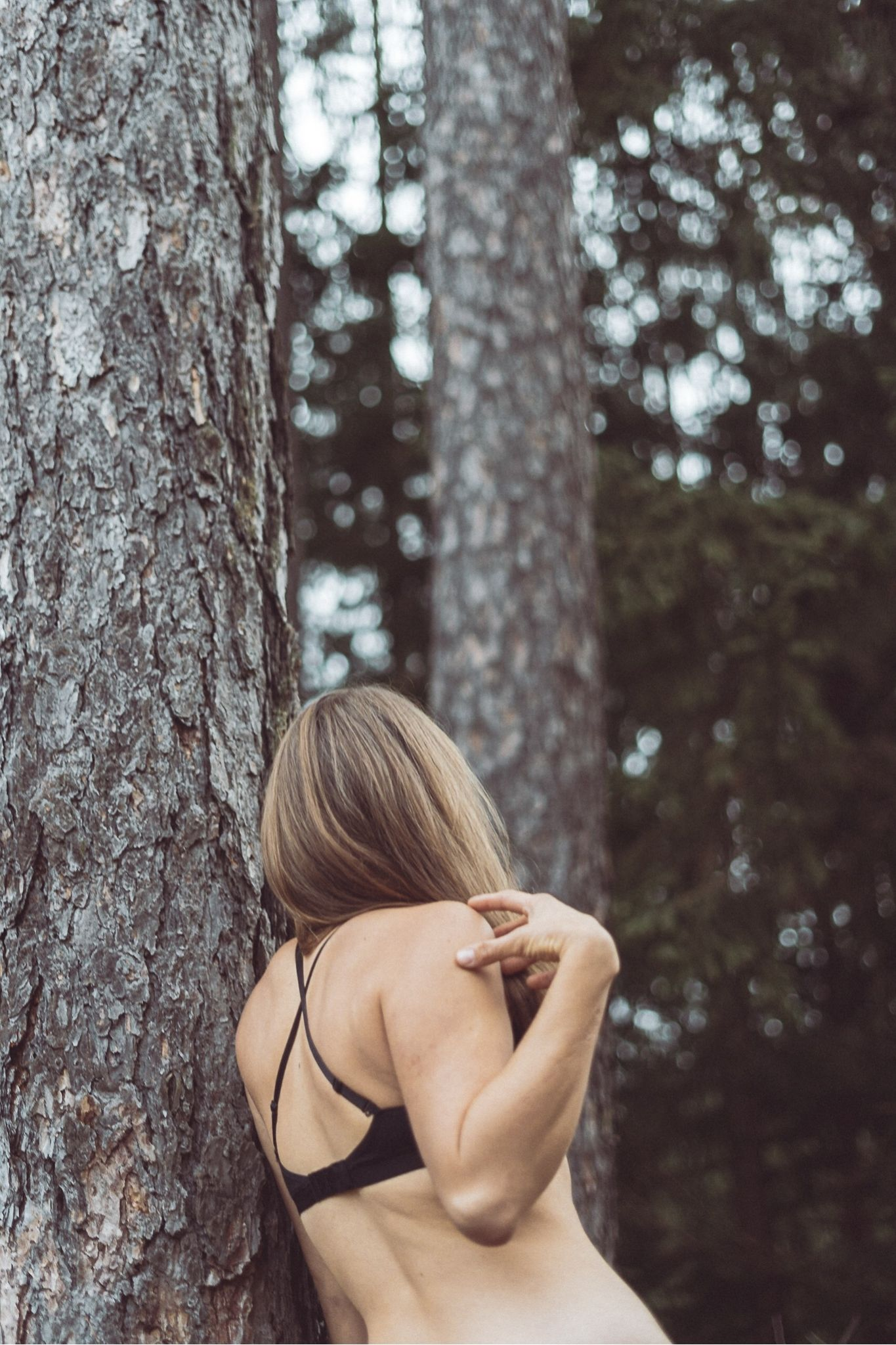 Girl standing in BON+BERG bra next to a tall tree.