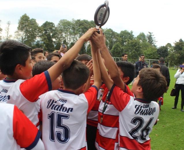 Seleccion de futbol celebrando triunfo con trofeo en manos