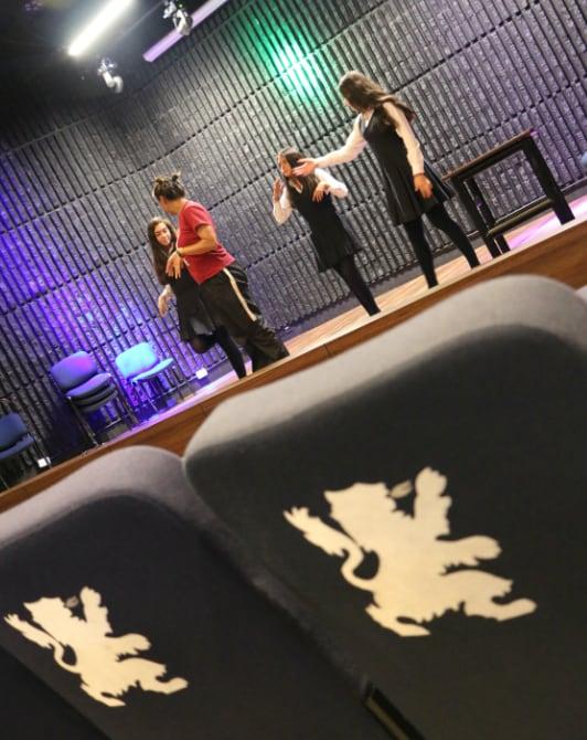 estudiantes ensayando obra de teatro