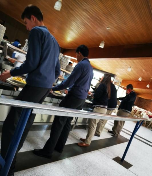 Estudiantes en la cafeteria en su hora de almuerzo