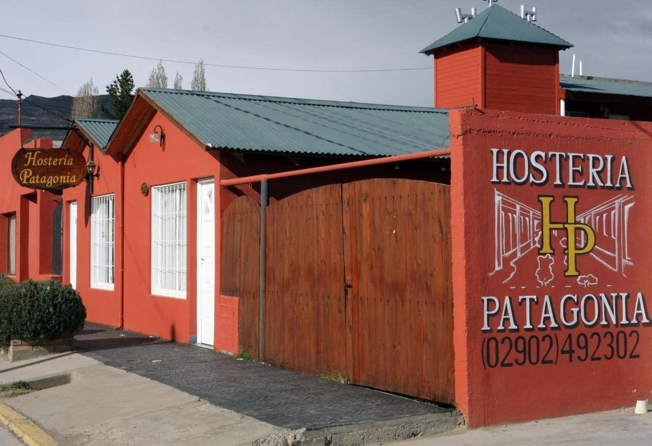 A red painted building that has a painted sign reading 'Hosteria Patagonia'