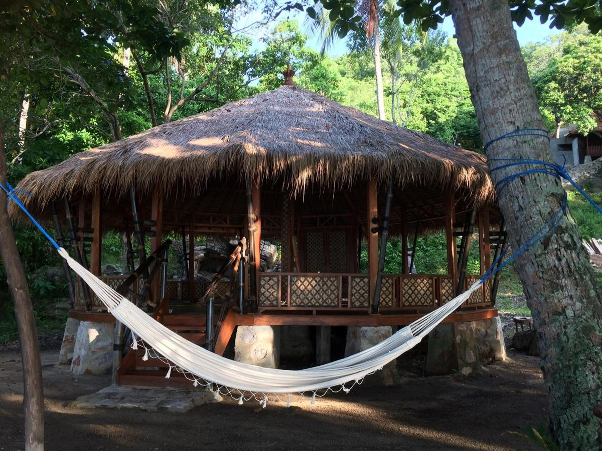A straw roofed open hut in the forest at Alam Kita, with a hammock strung up between two trees in front