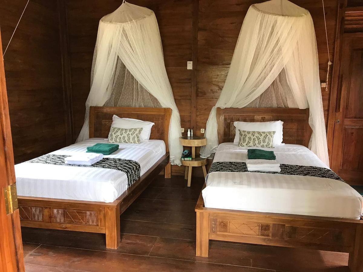 Two single beds at Alam Kita in a wooden panelled room, with mosquito nets above the beds