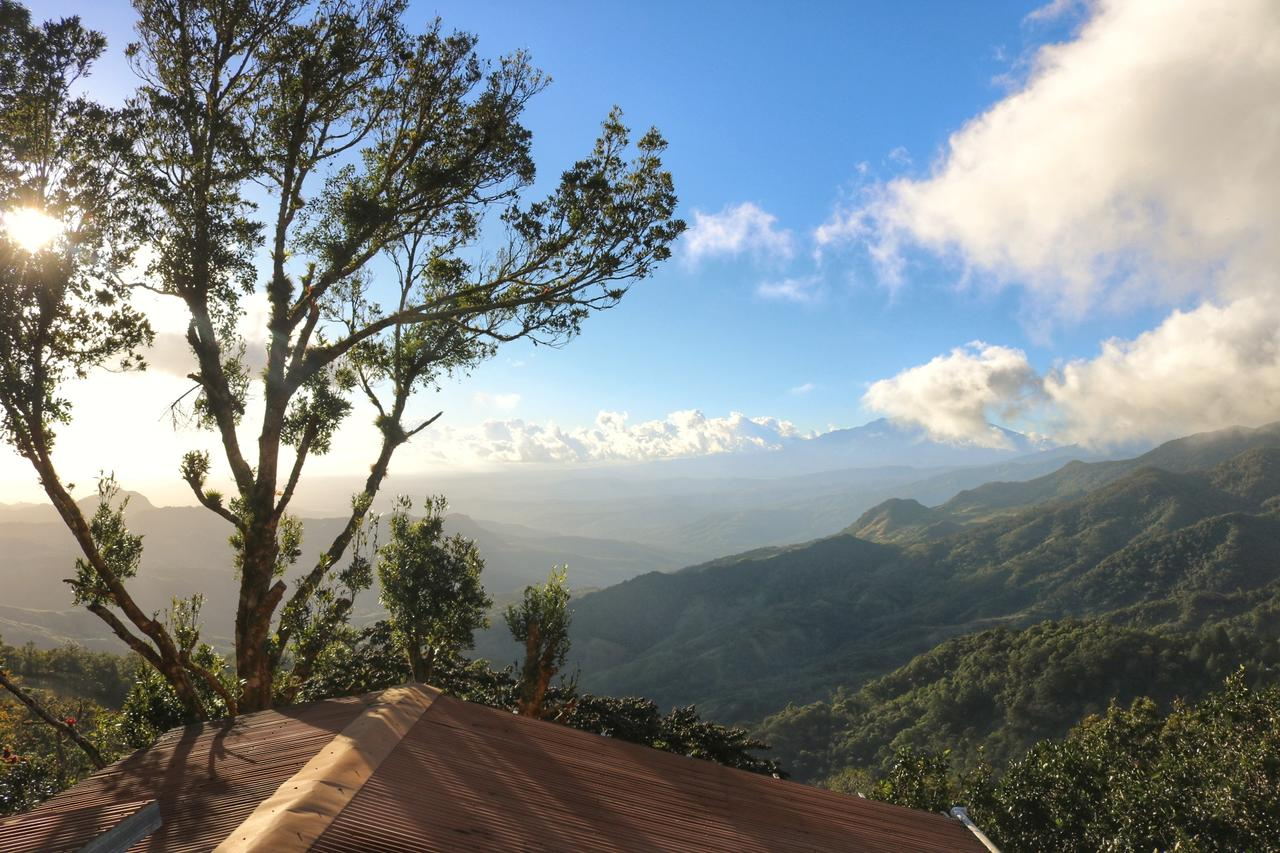 Over the roof of the hostel, the sun is low on the horizon, looking out across a valley in Panama - you can see green mountains and blue peaks in the distance