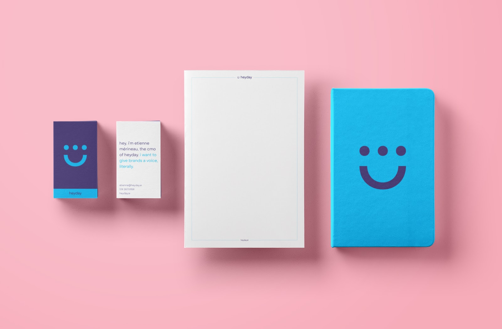 Heyday stationery such as business cards and notebooks put on a pink background.