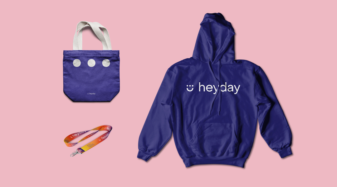 A tote bag, lanyard and hoodie on a pink background with Heyday logo
