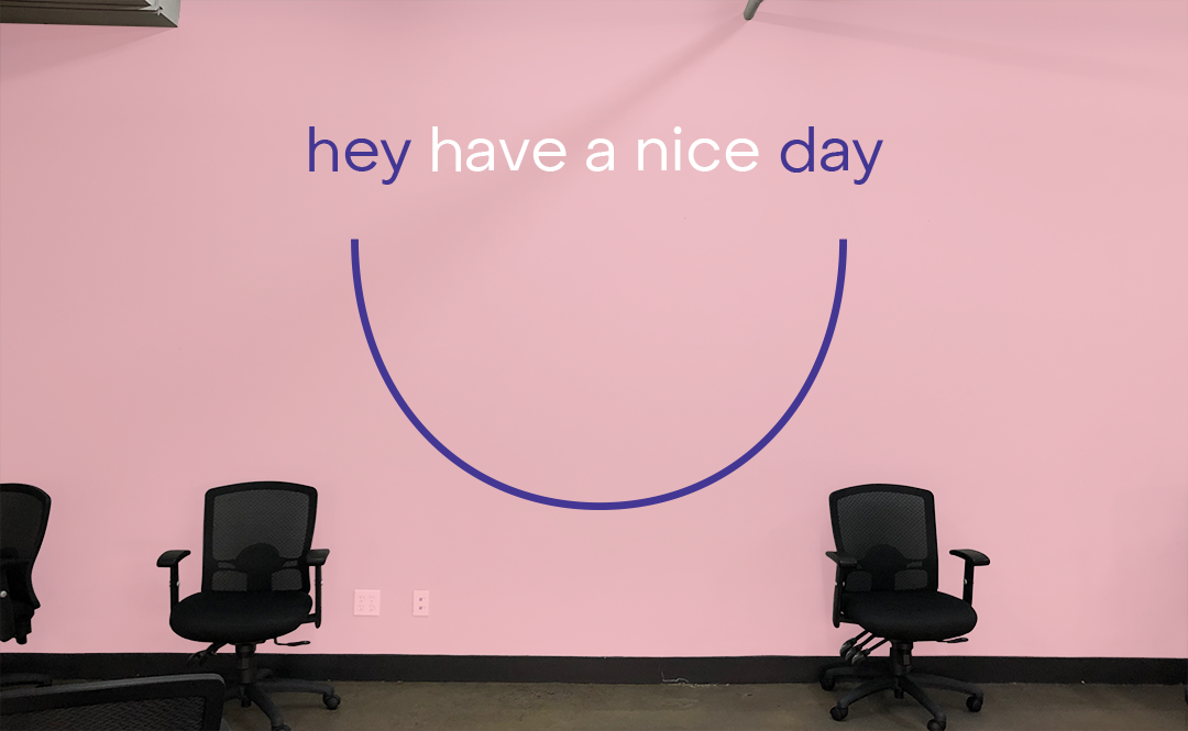 Hey have a nice day are written on a pink wall.