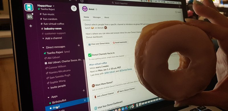 A real donut held in front of Donut, the slack app