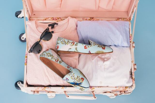 Organized suitcases with folded clothes shoes and sunglasses