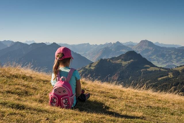 Child sitting on hill overlooking mountain backpacking with family