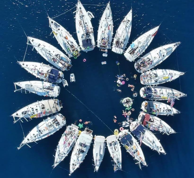 Circular formation of yachts in the ocean group partying
