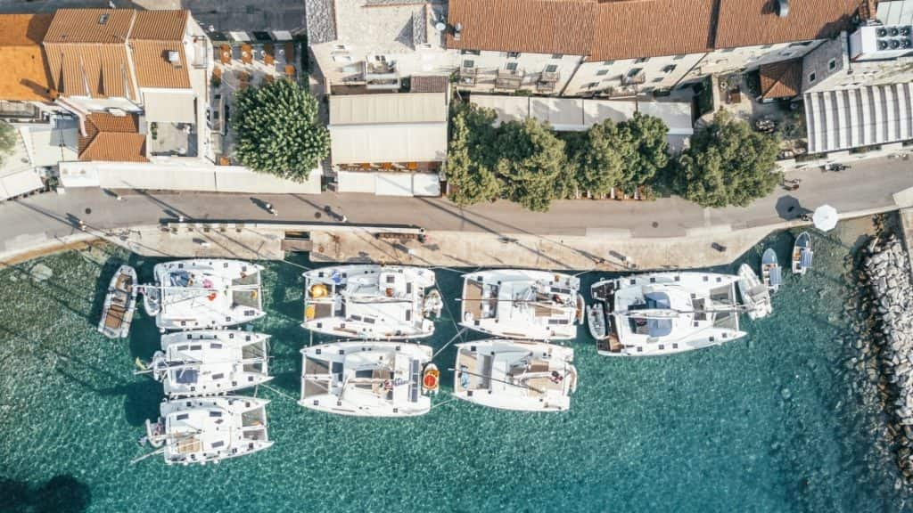 Yacht parked next to docks in clear ocean