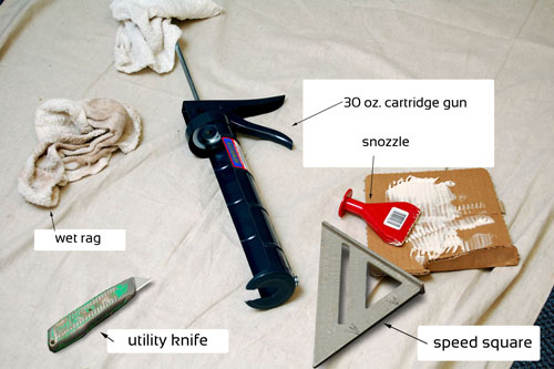 Material used to install vinyl wall base including wet rag, utility knife, cartridge gun, snozzle, and speed square.