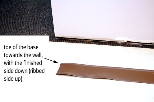 Strip of vinyl wall base with the ribbed side up and the toe of the base towards the wall.
