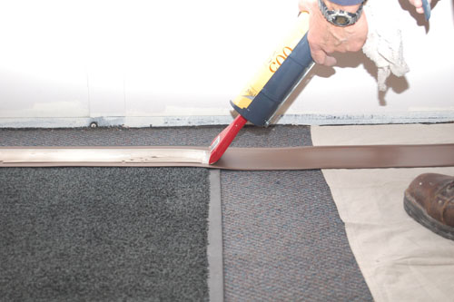 Man applies adhesive to the middle of the strip of vinyl wall base.