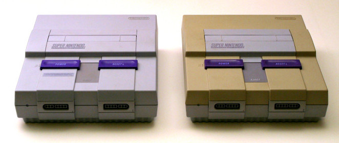 A new super nintendo next to an old, yellowing super nitendo