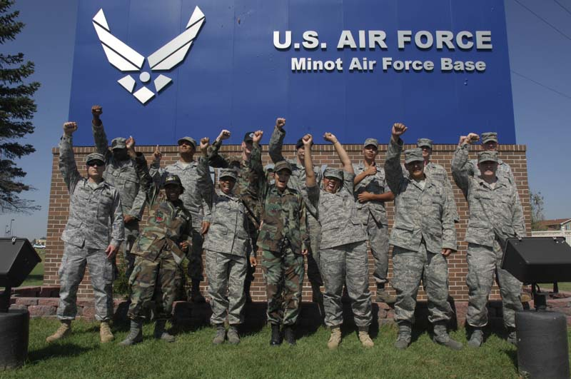 Men and women in military uniform lift their arms into the air with a Minot Air Force Base sign behind them