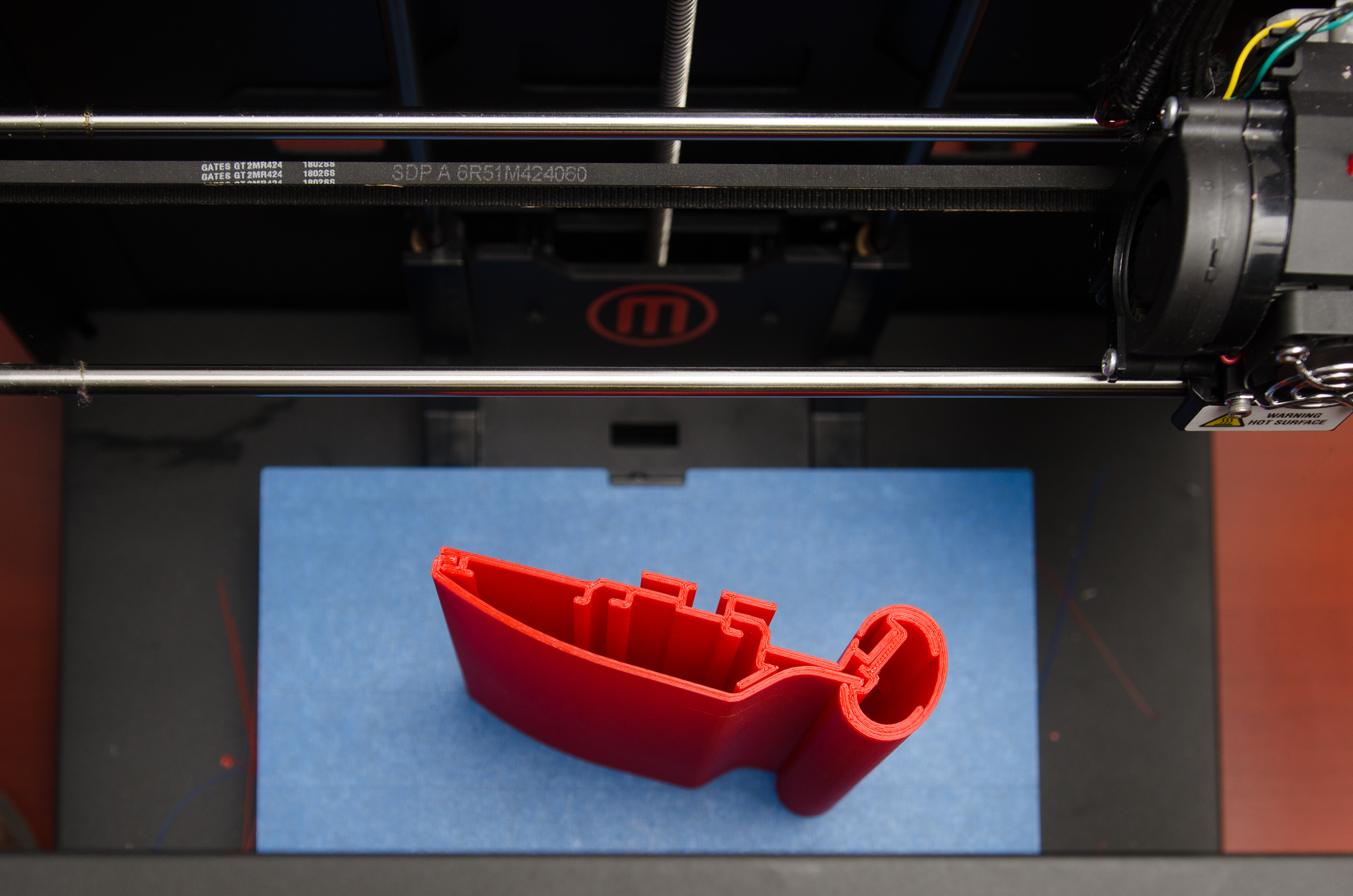 Red plastic prototype of a handrail sitting next to a 3D printer