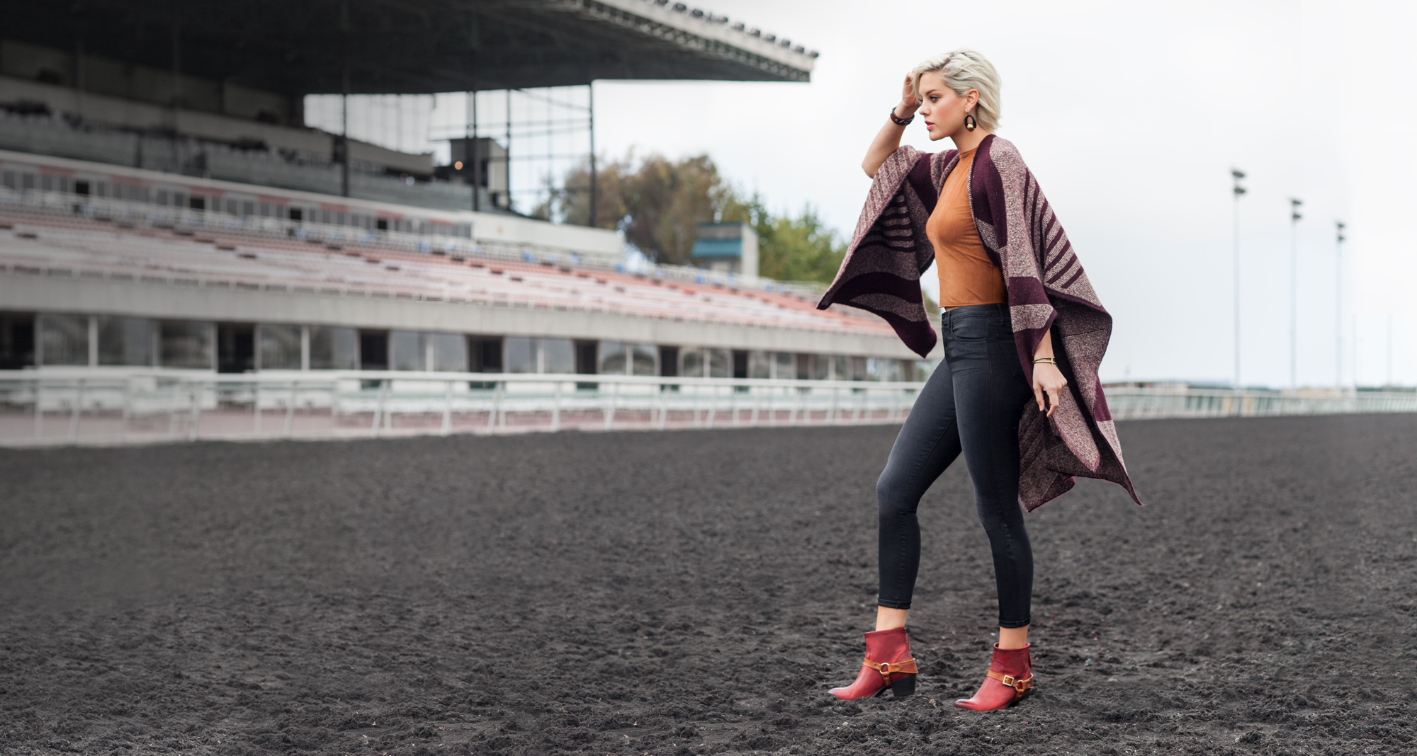 Women modeling fashionable Ariat boots on a horse race track