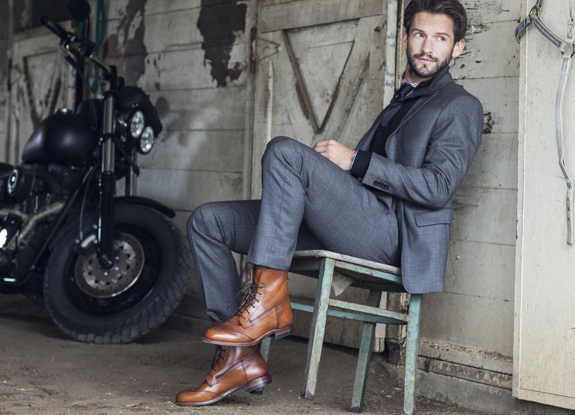Sharply dressed leaning back in chair modeling Ariat Two 24 fashionable boots