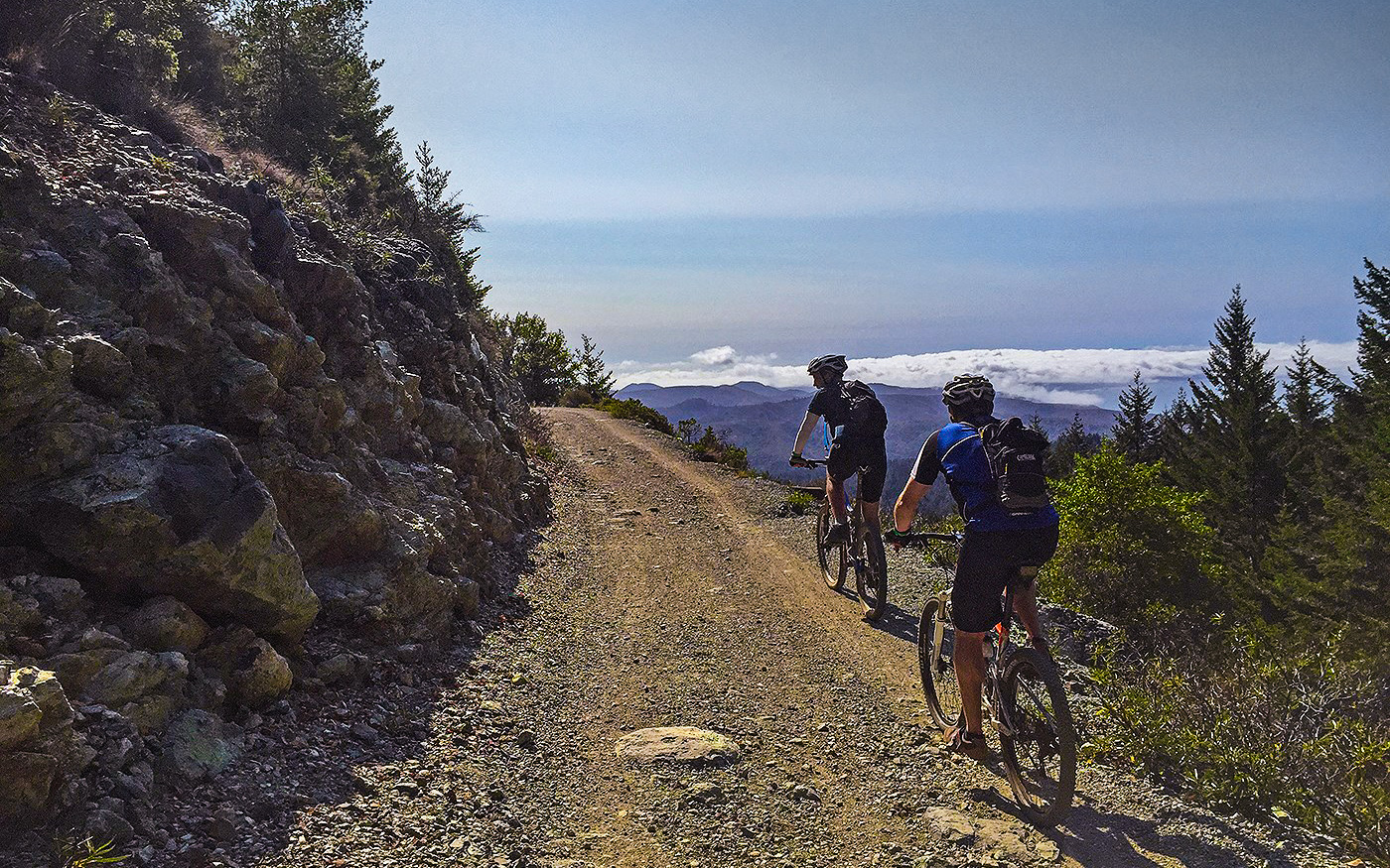 2 mountain bikers riding in high mountain trails with scenic views for Dirt Fondo event
