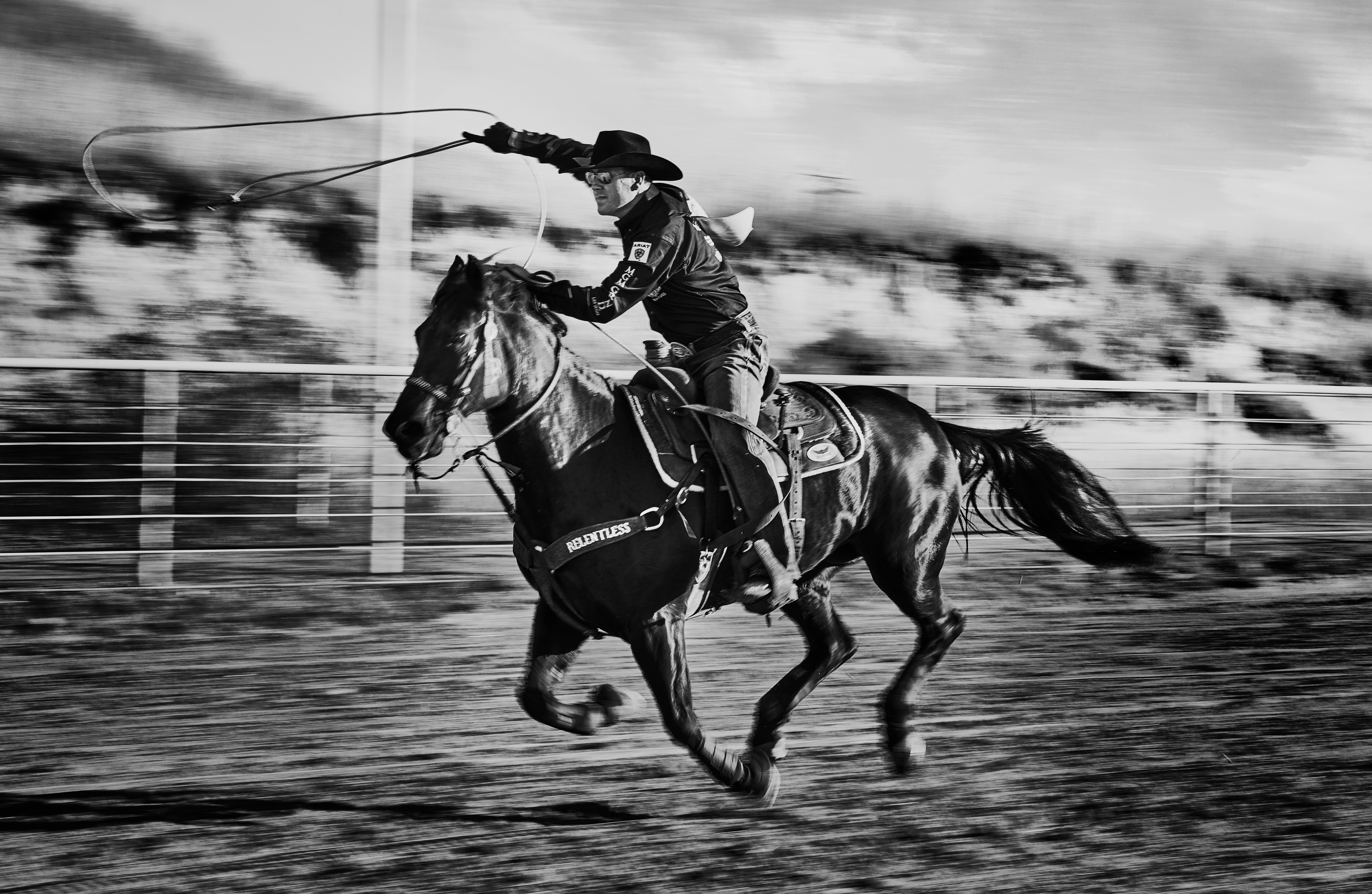Cowboy swinging lasso in air while riding horse in a dramatic black and white scene
