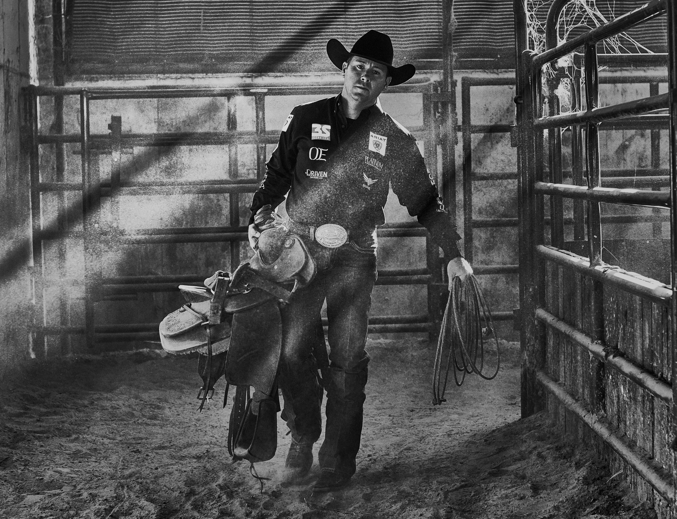 Dramatic scene of cowboy walking through stable with equestrian gear and rope