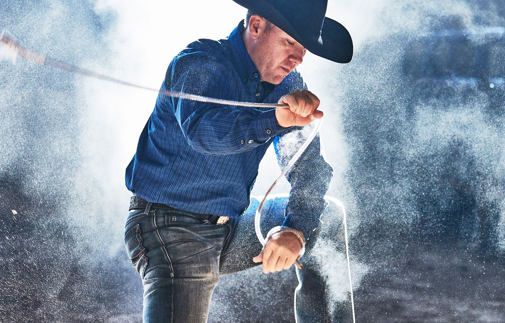 Bright lighting behind a cowboy lassoing out of the composition with rope in dramatic scene
