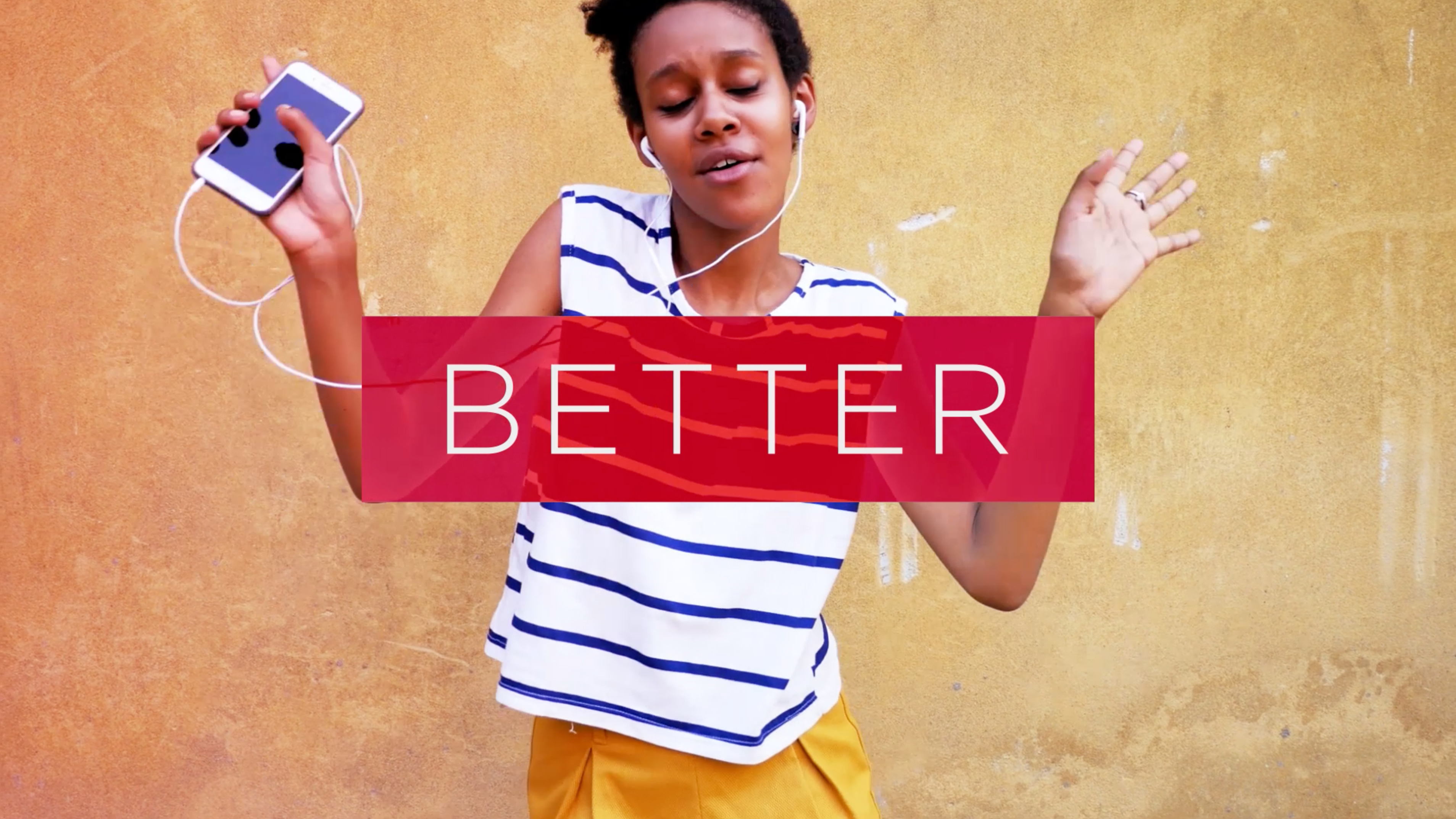 """Women with headphones and smartphone dancing with the word """"better"""" imposed over image"""