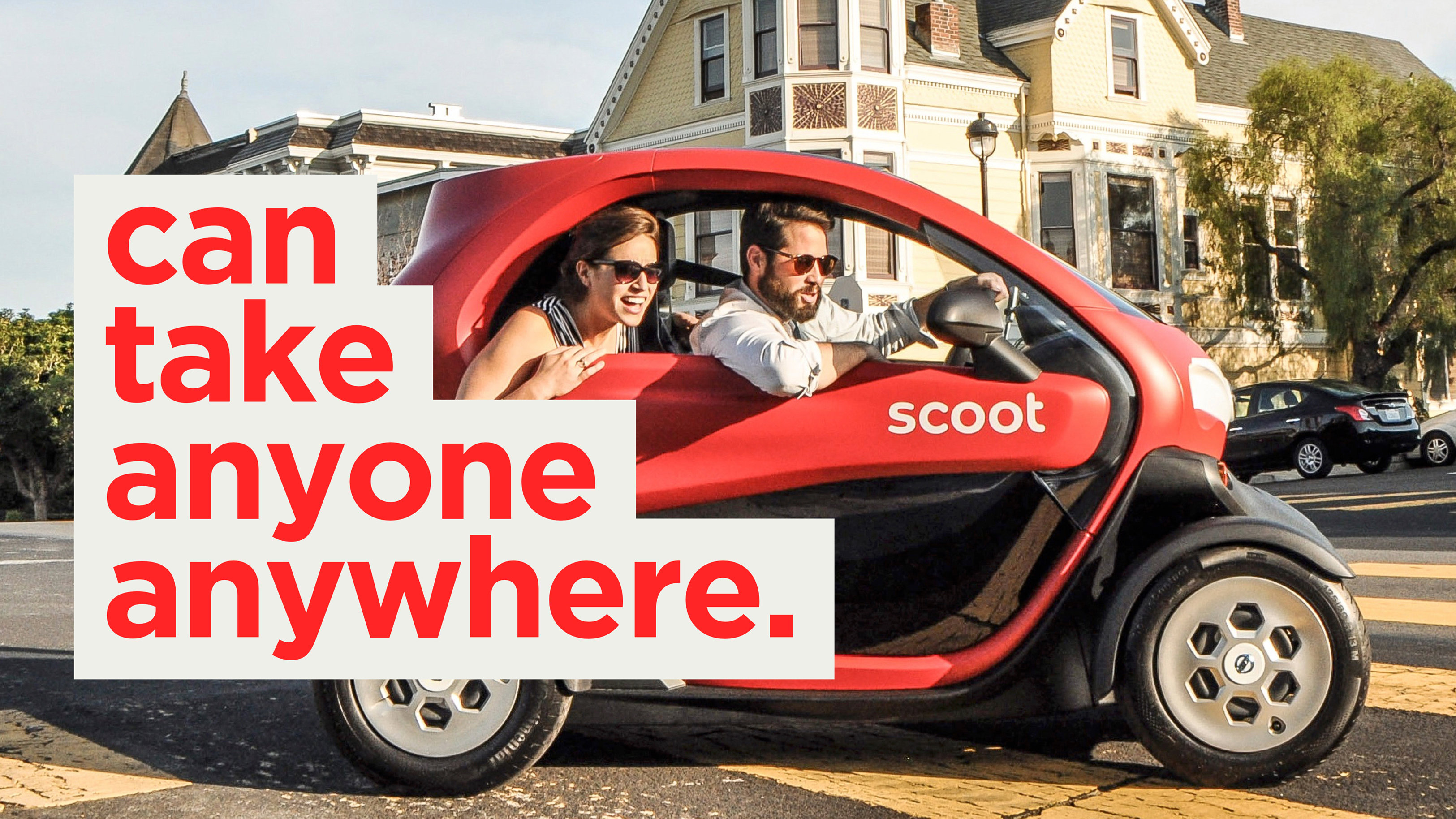"""Two people in small electric car making turn and leaning out window with large typography impose above the image that says """"can take anyone anywhere"""